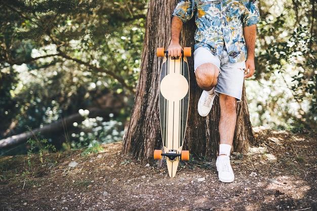 Mann, der auf baum mit skateboard sich lehnt