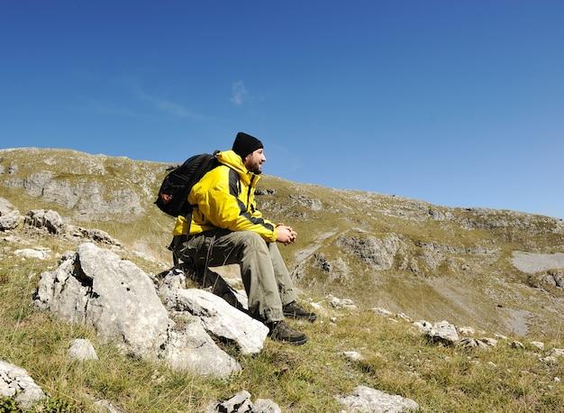 Mann, der auf berg sitzt