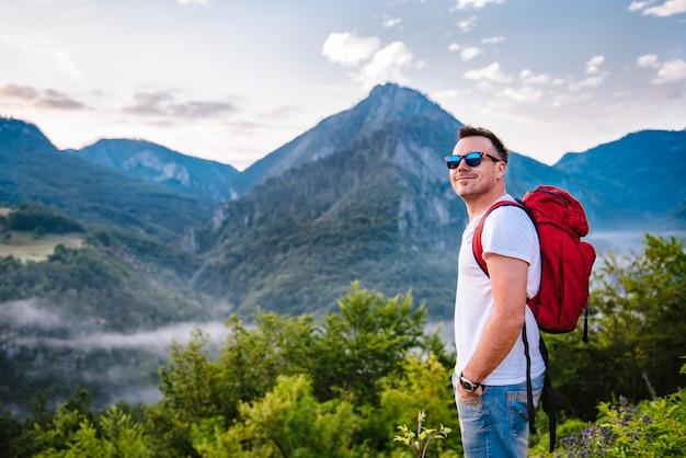 Mann, der auf berg und dem lächeln steht