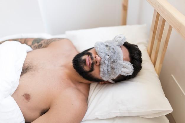 Mann, der auf bett mit schlafmaske schläft