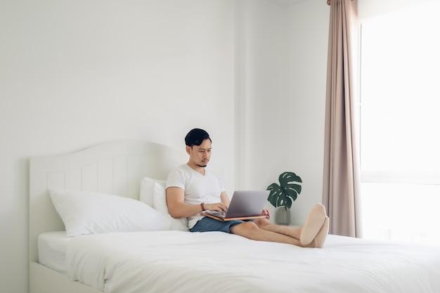 Mann, der auf bettarbeit an seinem laptop im gemütlichen weißen schlafzimmer liegt.