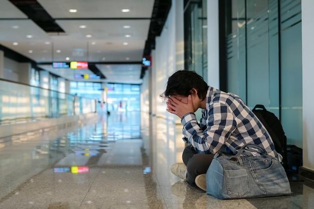 Mann, der auf boden im öffentlichen wegweg sitzt. er hielt die hand auf kopf und tasche und fühlte bedrängnis und stress, weil er sich nicht auf arbeitslosigkeit bewerben konnte