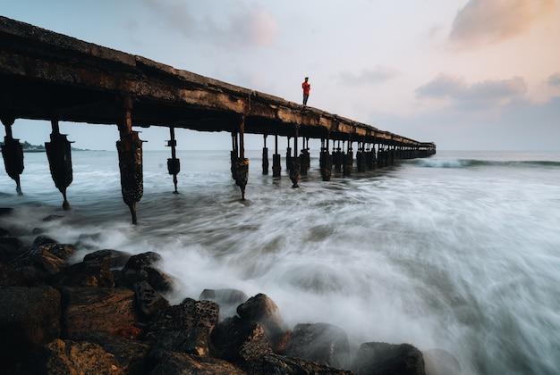 Mann, der auf brocken sea bridge steht