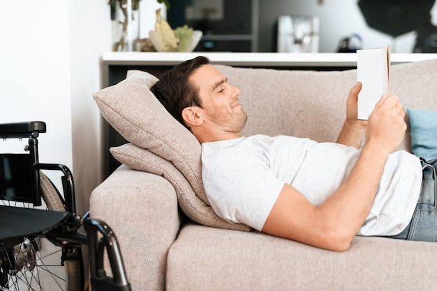 Mann, der auf couch mit tablet nahe rollstuhl liegt