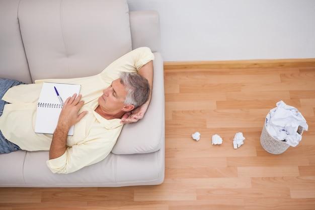 Mann, der auf couch mit zerknitterten papieren liegt