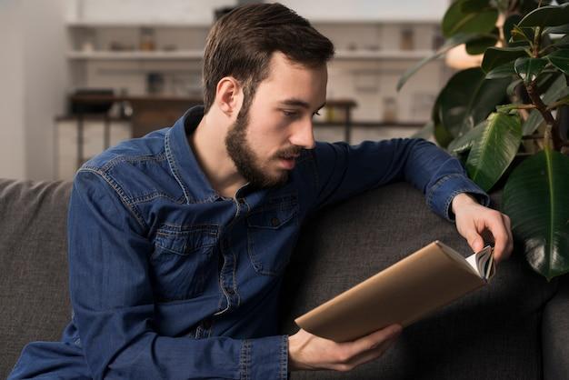 Mann, der auf couch und lesebuch sitzt