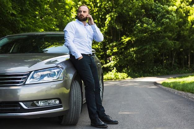 Mann, der auf dem auto spricht auf smartphone sich lehnt