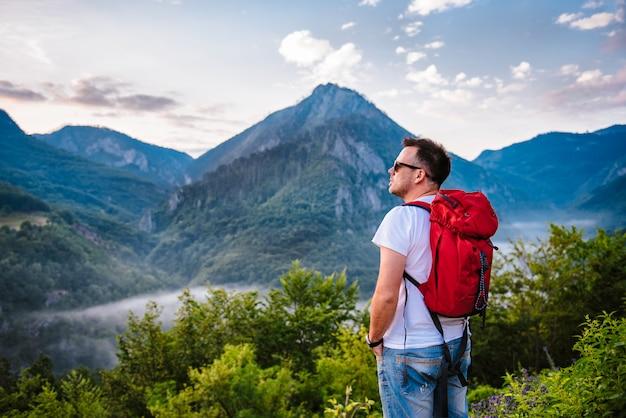 Mann, der auf dem berg wandert und sonnenaufgang betrachtet