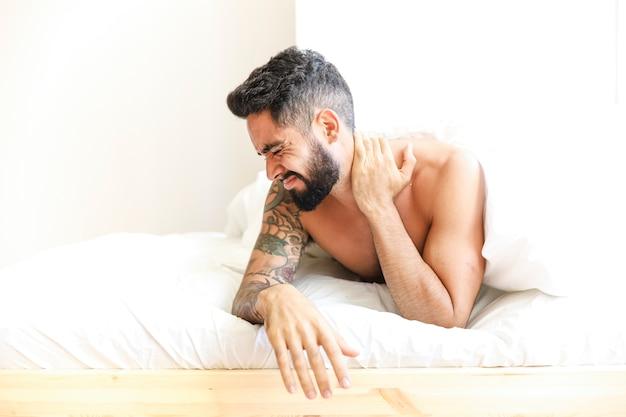 Mann, der auf dem bett leidet unter den nackenschmerzen liegt