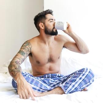 Mann, der auf dem bett trinkt kaffee sitzt