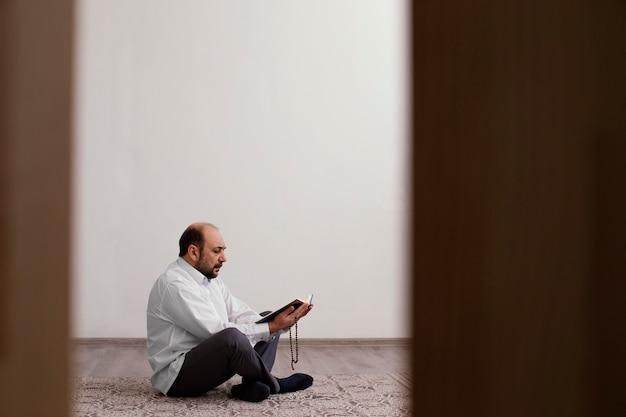 Mann, der auf dem boden drinnen betet