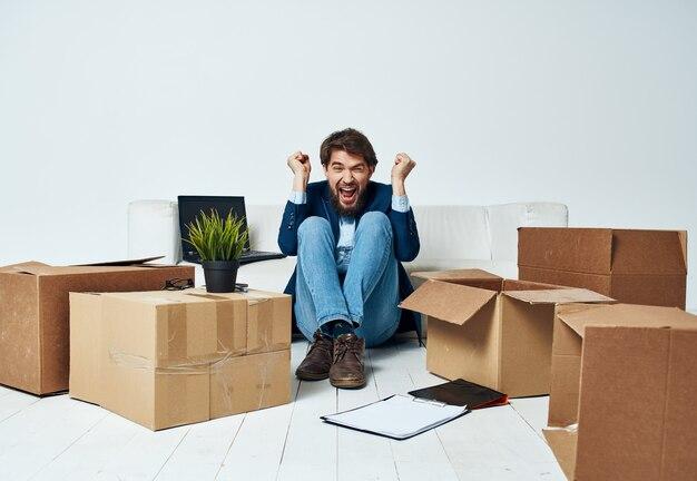 Mann, der auf dem boden mit den kisten der sachen sitzt, die zum büro bewegen, das lebensstil auspackt.