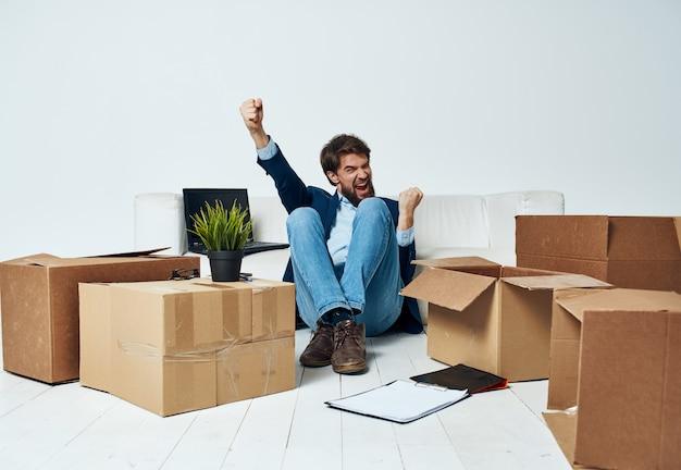 Mann, der auf dem boden mit kisten der sachen sitzt, die zum büro bewegen, das lebensstil auspackt.