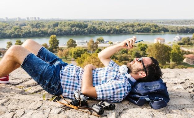 Mann, der auf dem boden unter verwendung des mobiltelefons liegt