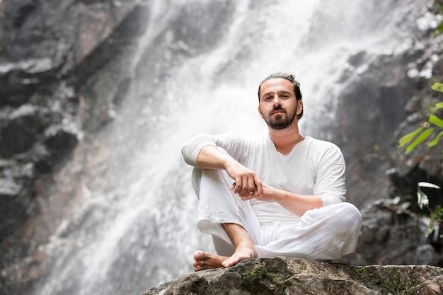 Mann, der auf dem felsen unter tropischem wasserfall sitzt