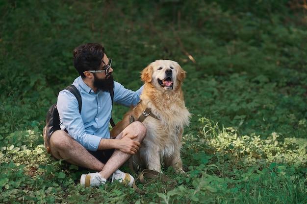 Mann, der auf dem gras ruht, das gekreuzte beine mit seinem hund sitzt