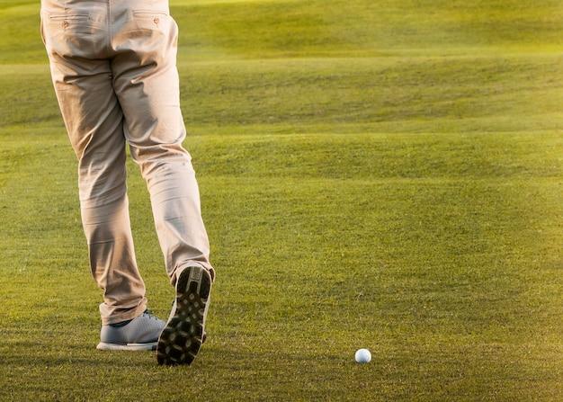 Mann, der auf dem grasbewachsenen golffeld spielt