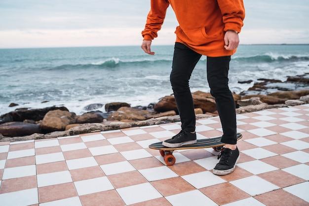Mann, der auf dem skateboard übt.