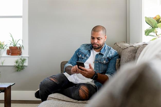 Mann, der auf dem smartphone eine sms schreibt und zu hause auf einer couch sitzt