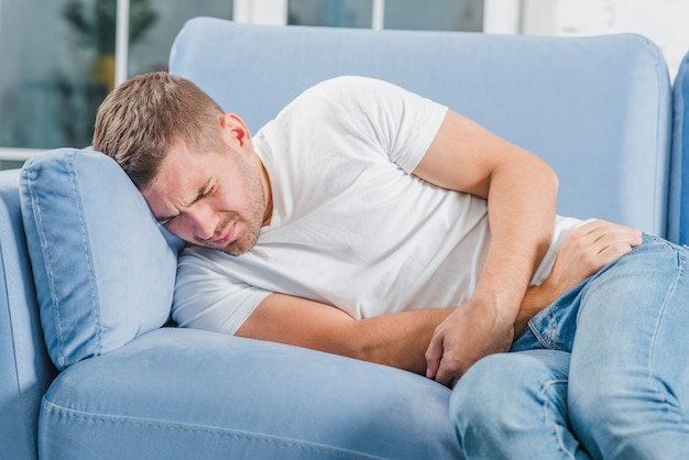 Mann, der auf dem sofa liegt, das starke magenschmerzen hat