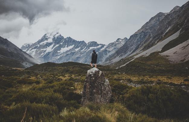 Mann, der auf dem stein in hooker valley track mit blick auf mount cook in neuseeland steht