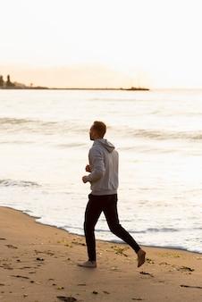 Mann, der auf dem strand geht