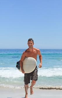 Mann, der auf den strand mit seinem surfbrett läuft