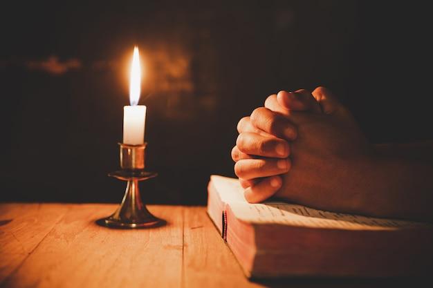 Mann, der auf der bibel in den selektiven fokus der hellen kerzen betet