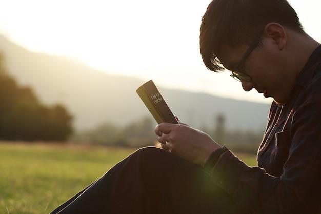 Mann, der auf der heiligen bibel auf einem feld während eines schönen sonnenuntergangs betet, der mit geschlossenen augen sitzt