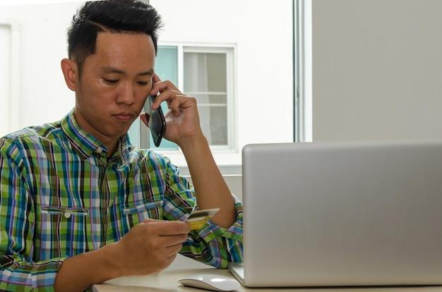 Mann, der auf der telefonfinanzierungskreditkarteninformation spricht