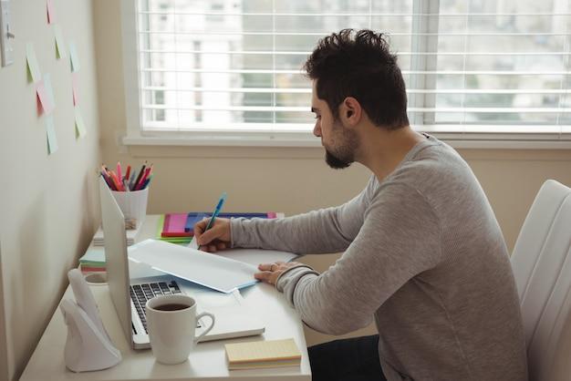 Mann, der auf dokument schreibt, während er am schreibtisch sitzt