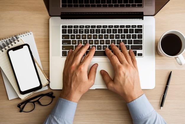Mann, der auf draufsicht des laptops schreibt