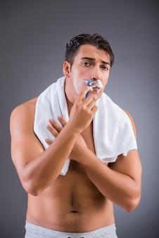 Mann, der auf dunklem hintergrund sich rasiert