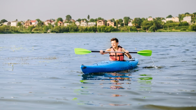 Mann, der auf einem aufblasbaren kajak über see kayak fährt