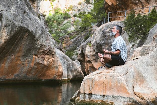 Mann, der auf einem felsen am fuße eines gebirgsflusses meditiert