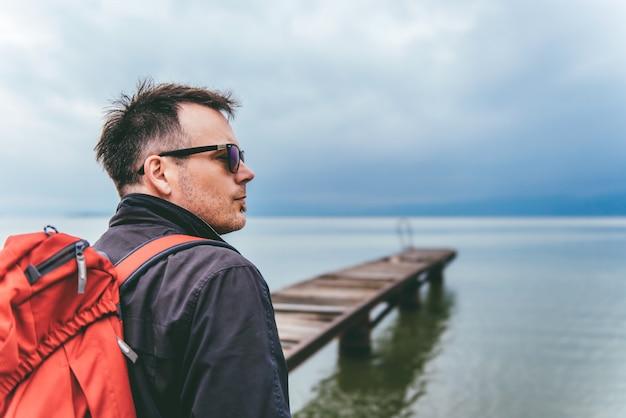 Mann, der auf einem flussdock steht und seitlich schaut