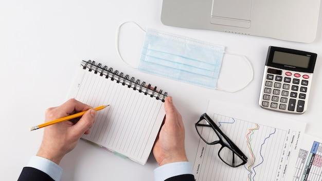 Mann, der auf einem leeren notizblock neben finanzelementen schreibt