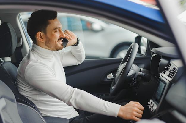 Mann, der auf einem mobiltelefon beim autofahren spricht.