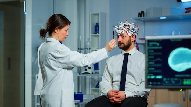 Mann, der auf einem neurologischen stuhl mit gehirnwellen-scanning-headset sitzt, während der forscher den gesundheitszustand in der zwischenablage untersucht. ärzte, die im gehirnstudienlabor mit monitoren arbeiten, die eeg-messwerte anzeigen.