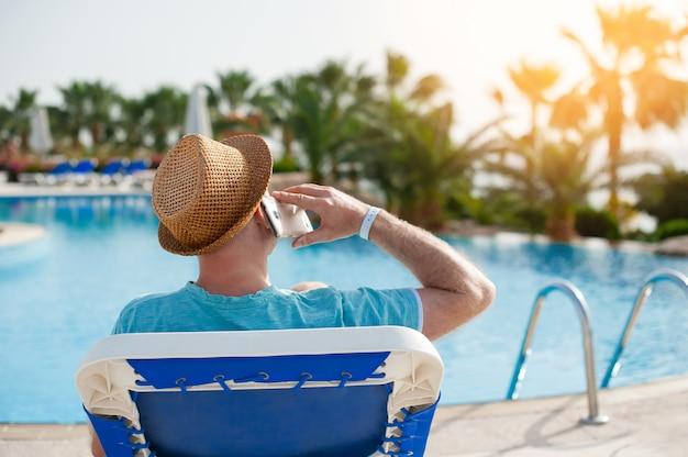 Mann, der auf einem ruhesessel liegt und an einem telefon nahe dem pool spricht
