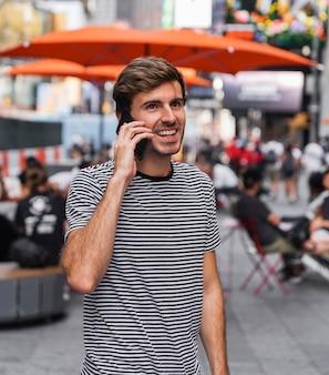 Mann, der auf einem smartphone vor einer terrasse spricht