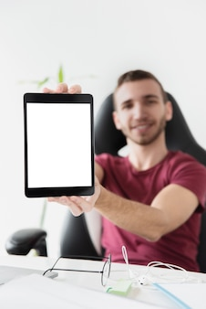 Mann, der auf einem spielstuhl sitzt und seine tablette zeigt
