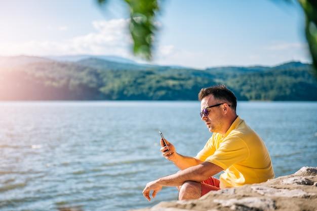 Mann, der auf einem strand sitzt und intelligentes telefon verwendet