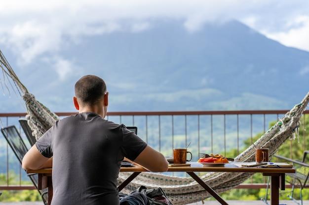 Mann, der auf einem tisch mit frühstück sitzt, während er mit blick auf einen vulkan vor ihm arbeitet. costa rica