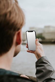 Mann, der auf einen leeren smartphone-bildschirm schaut