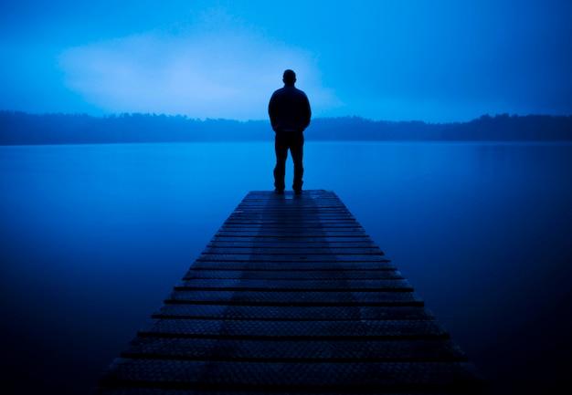 Mann, der auf einer anlegestelle an einem ruhigen see steht.