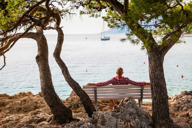 Mann, der auf einer bank am ufer eines kleinen dorfes brela, makarska riviera, kroatien sitzt
