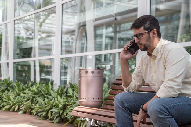 Mann, der auf einer bank spricht am telefon sitzt