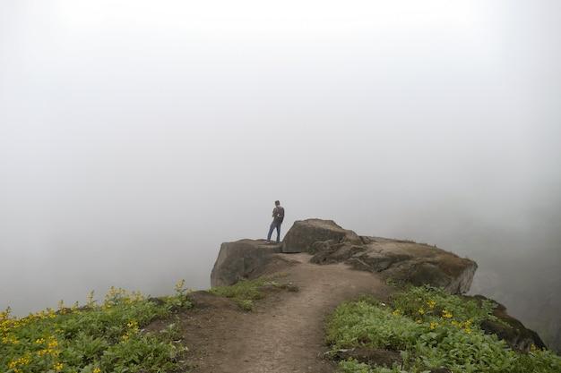 Mann, der auf einer klippe in einem tal steht und auf die nebelstraße der blumen schaut