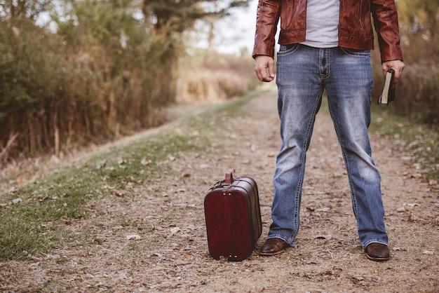Mann, der auf einer leeren straße nahe seinem alten koffer steht und die bibel mit unscharfem hintergrund hält